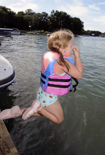 Little girl jumping off dock