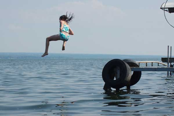 Photo of a girl jumping into a lake for a swim