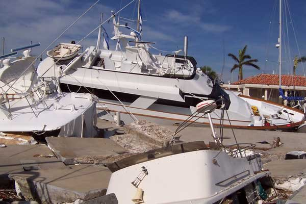 Photo of hurricane-damaged boats piled on top of each at a marina