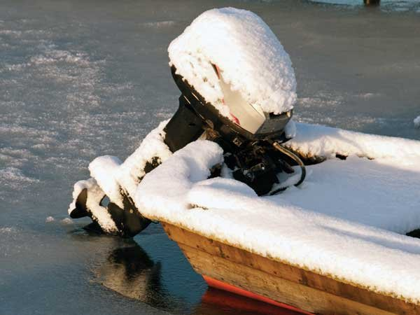 Photo of an outboard engine with snow on top of it