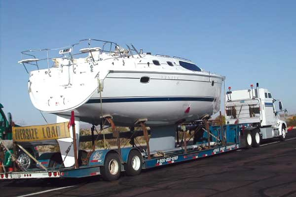 Photo of a boat being transport on a large flatbed truck