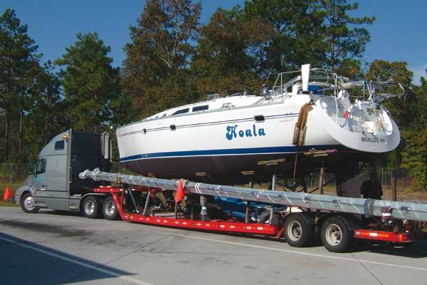 Photo of large sailboat being transported on a flatbed truck with the mast well protected