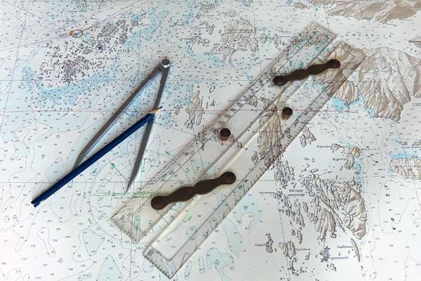 Photo of paper navigational chart and compass